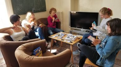 A group of friends seated around a table playing a game like Telestrations