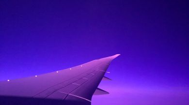 View of airplane wing in flight at night