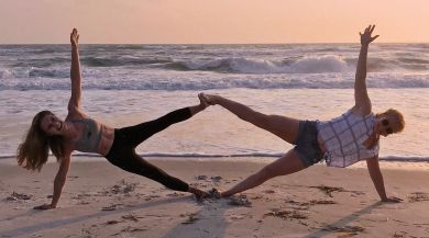 Girls practicing yoga on the beach