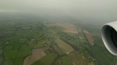 Thick fog hovers over a sea of green, viewed from the window of an airplane