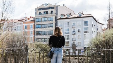 A student looks out at a row of apartments in Madrid