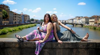 two students sitting on bridge overlooking river in siena, italy