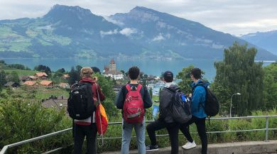 students standing in front of a lake and mountain