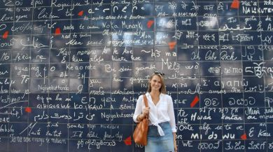 student standing in front of wall with love in multiple language
