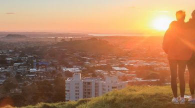 two students standing on Mt Eden overlooking Auckland at sunset