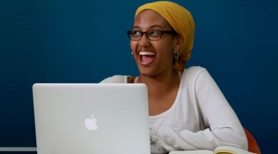 student smiling behind a laptop with bright blue wall behind her