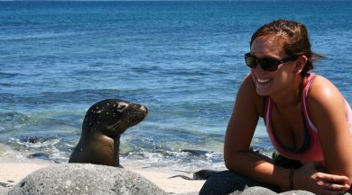 student smiling at a seal near the ocean