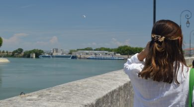 Student walking by river in Arles