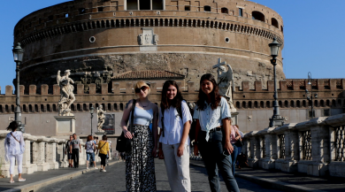 three students smiling in front of Roman landmark