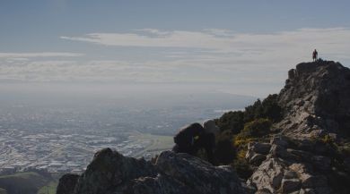 student standing on mountain overlooking Christchurch
