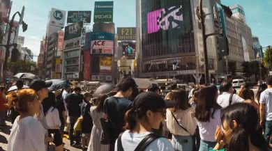 Crowds cross the large Shibuya Crossing in Tokyo.