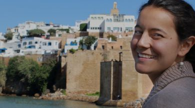 student smiling over her shoulder with city of rabat in the background