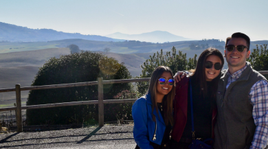 three students smiling in front of tuscany vineyard