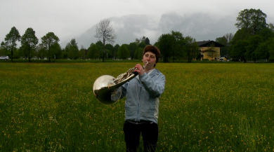 student standing in grass playing french horn