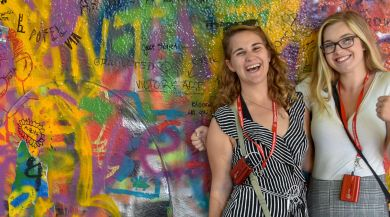 two students smiling in front of graffiti wall in Austria