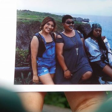 Polaroid photo in Samekh's hand, featuring Sam and two friends smiling and posing alongside a coastline