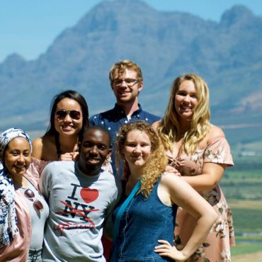 group of students in South Africa standing in front of mountain landscape