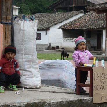 Two Ecuadorian children selling bug spray in a small town