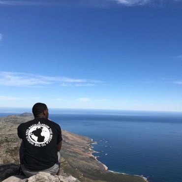 Ameer sitting on rock ledge overlooking the ocean in Cape Town