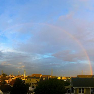 Full rainbow in blue sky with clouds over town