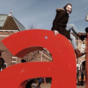 Sitting on the I Amsterdam Sign