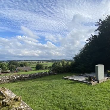 Am image featuring gravestones that overlooking the rolling valleys of County Meat