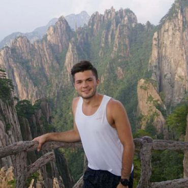 Nolan Derr in front of mountain landscape while studying abroad in China