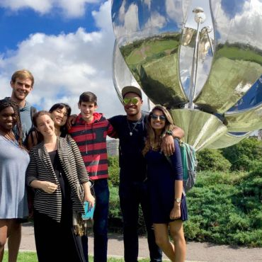 students pose in front of Floralis Generica sculpture in buenos aires