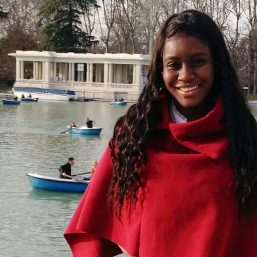 sydni williams in red top standing in front of pond with boats
