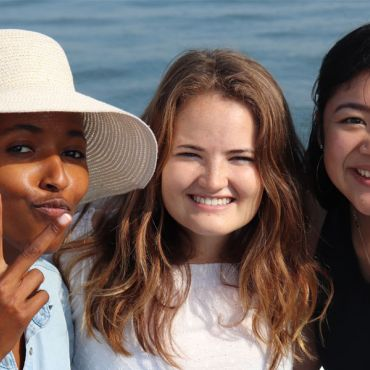 Three young women smiling together on a boat.