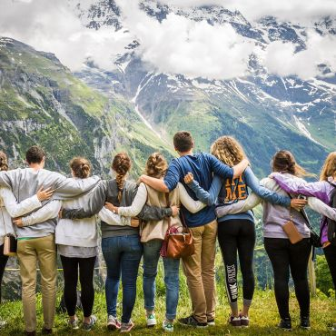 Students facing a mountain range with their arms around each other