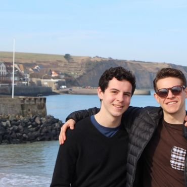 two students studying abroad in france in front of beach
