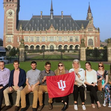 Group of IU Students on a Faculty-Led Study Abroad Program in Amsterdam holding a red IU flag