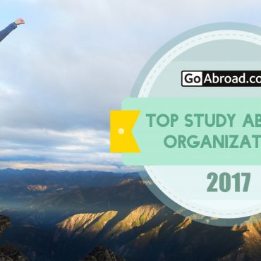 student posing on rocks with Go Abroad Top Study Abroad Organization 2017 Logo