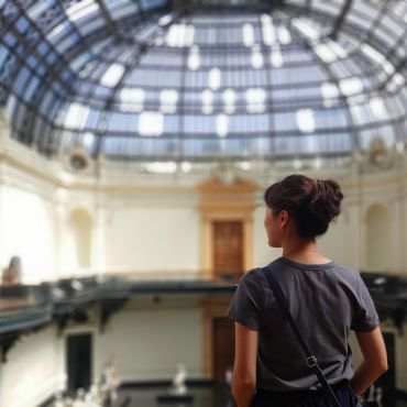 study abroad student with her back turned, looking thoughtfully out over a museum hall with a glass dome ceiling