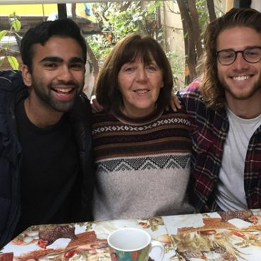 Collin Thomas sitting at table with host family studying abroad in Chile