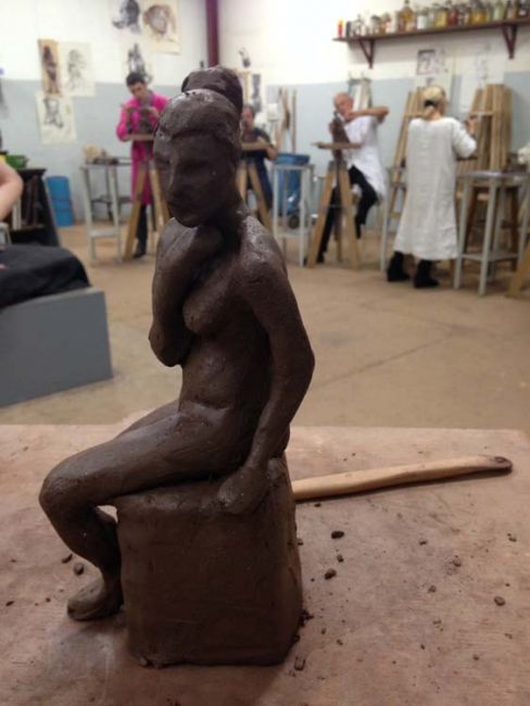 Students forming figures out of clay