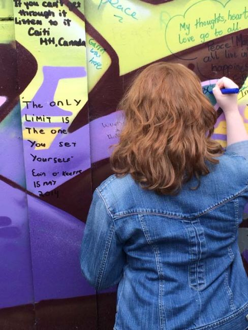 Student signing the wall in Dublin