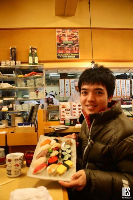 Student with a plate of sushi rolls