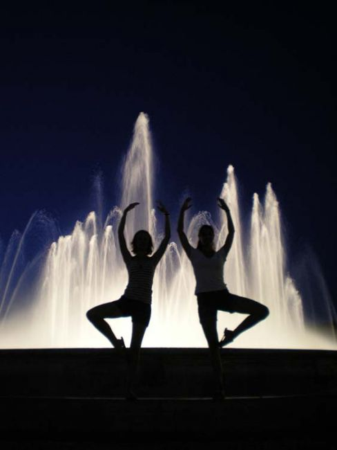 Students posing by a fountain at nighttime