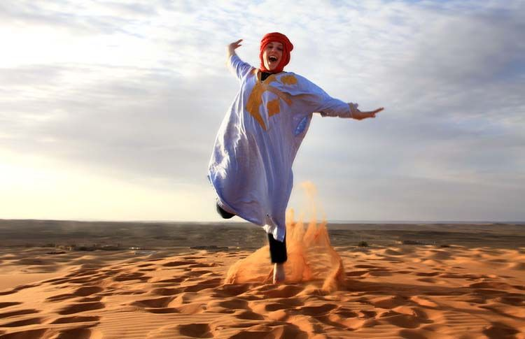 Student jumping in sand