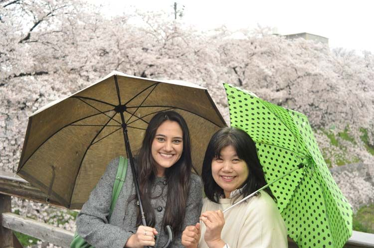 Student and host mother holding umbrellas