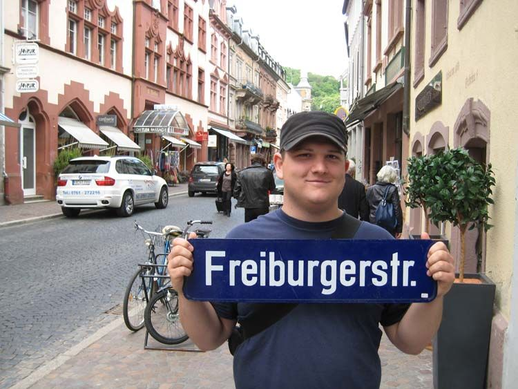 Student holding on to a Freiburg sign