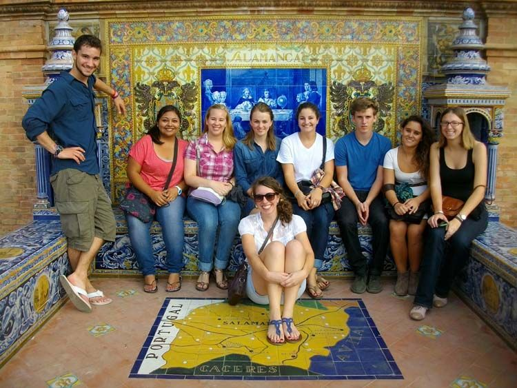 Students seated in front of tiled artwork
