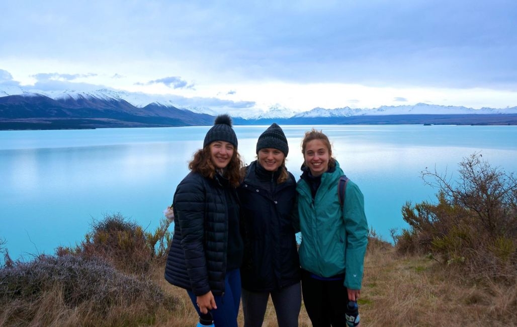 Three students pose in front of a bright blue glacial lake.