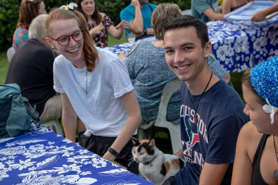 Group of students eats dinner with locals and a friendly cat.