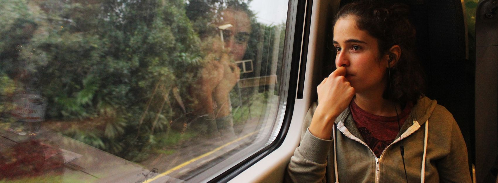 student sitting on train looking out the window with headphones in their ears