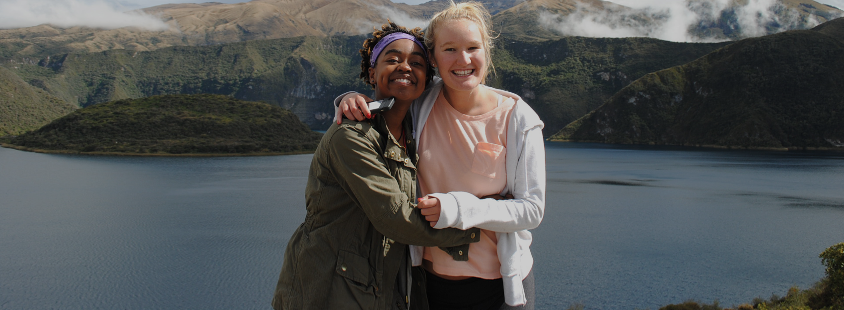 two students hugging in front of a lake in ecuador
