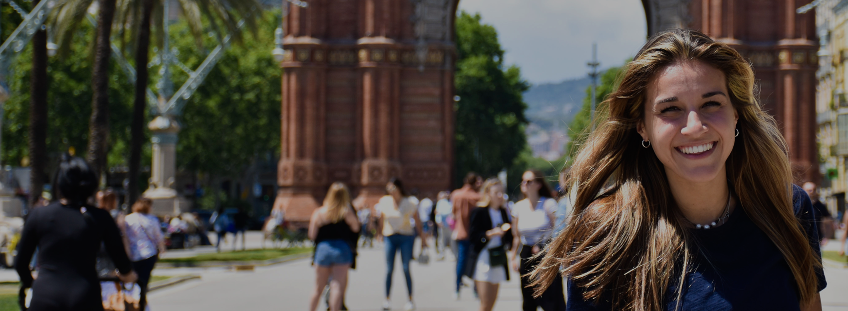 Female student with long hair in front of Arc de Triomf in Barcelona