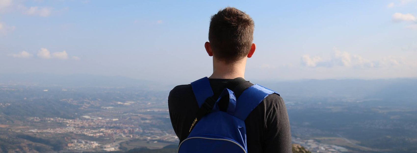 Study abroad student with a backpack on overlooking the view of a city